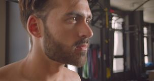 Zbliżenie portret bez koszuli mięśniowy zdecydowany caucasian mężczyzna opracowywa z dumbbells z wysiłek pozycją w zbiory wideo