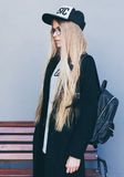 Zbliżenie portret blondynki dziewczyna z długim ostrzyżeniem Modniś, insagram styl Jest ubranym czarną modną suknię, szkła Zdjęcia Royalty Free