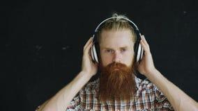 Zbliżenie portret brodaty młody człowiek w hełmofonach słucha muzyczny i patrzeć w kamery ono uśmiecha się Obrazy Royalty Free