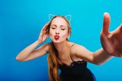 Zbliżenie portret daje buziakowi kamera urocza dziewczyna, bierze selfie na błękitnym tle, dama na przyjęciu, maskarada zdjęcie royalty free