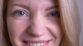 Zbliżenie portret dorosła atrakcyjna caucasian żeńska twarz z oczami patrzeje kamerę z szczęśliwym wyrazem twarzy z zdjęcie wideo