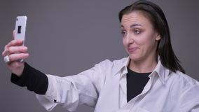 Zbliżenie portret dorosła atrakcyjna caucasian kobieta ma wideo wzywa telefon i ono uśmiecha się z tłem zbiory wideo