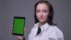 Zbliżenie portret dorosła atrakcyjna caucasian kobieta używa pastylkę i pokazywać zieleń ekran kamera z zbiory wideo