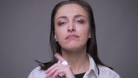 Zbliżenie portret dorosła atrakcyjna caucasian kobieta w białej koszulowej patrzeje kamerze z brutalnym wyrażeniem z zbiory