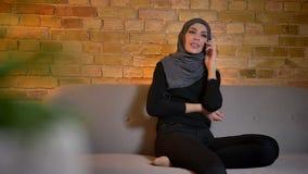 Zbliżenie portret dorosła atrakcyjna muzułmańska kobieta opowiada na telefonie w hijab podczas gdy siedzący na leżance indoors w  zbiory