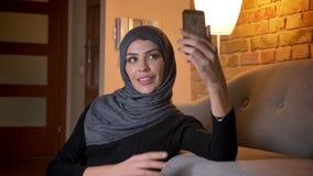 Zbliżenie portret dorosła atrakcyjna muzułmańska kobieta w hijab bierze selfies na telefonie podczas gdy siedzący na podłodze wew zbiory wideo