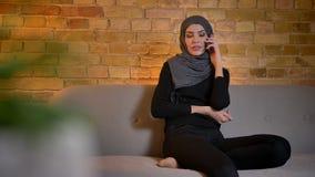 Zbliżenie portret dorosła atrakcyjna muzułmańska kobieta w hijab ma rozmowę na telefonie podczas gdy siedzący na zbiory