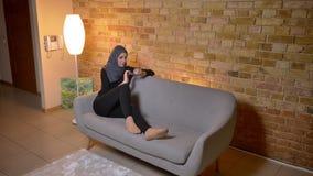 Zbliżenie portret dorosła atrakcyjna muzułmańska kobieta w hijab surfingu sieci na telefonie podczas gdy siedzieć laidback na leż zdjęcie wideo