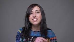 Zbliżenie portret dorosła caucasian brunetki kobieta opowiada na kamerze uśmiecha się lotniczego buziaka z tłem i robi zbiory
