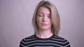 Zbliżenie portret dorosłej atrakcyjnej blondynki caucasian żeński falowanie jej głowa mówić nie patrzejący kamerę z tłem zbiory wideo