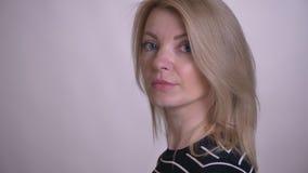 Zbliżenie portret dorosłej atrakcyjnej blondynki caucasian żeński kręcenie i patrzeć kamerę z tłem odizolowywającym dalej zbiory