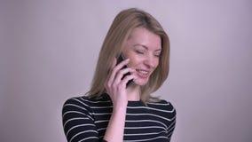 Zbliżenie portret dorosłej atrakcyjnej blondynki caucasian kobieta ma rozmowę telefoniczą i ono uśmiecha się z tłem odizolowywają zdjęcie wideo