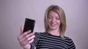 Zbliżenie portret dorosłej atrakcyjnej blondynki caucasian kobieta ma wideo wzywa telefon i ono uśmiecha się z zbiory wideo