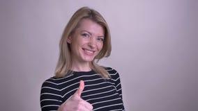Zbliżenie portret dorosłej atrakcyjnej blondynki caucasian kobieta pokazuje kciuk w górę patrzeć kamerę z tłem zbiory wideo