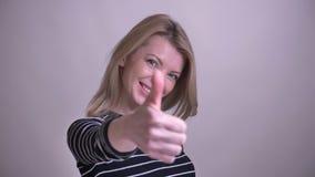 Zbliżenie portret dorosłej atrakcyjnej blondynki caucasian kobieta pokazuje kciuk w górę uśmiechać się patrzeje kamerę z zbiory wideo