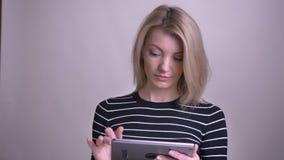 Zbliżenie portret dorosłej atrakcyjnej blondynki caucasian kobieta używa pastylkę i pokazywać zieleń ekran kamery ono uśmiecha si zdjęcie wideo