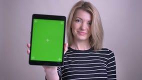 Zbliżenie portret dorosłej atrakcyjnej blondynki caucasian kobieta używa pastylkę i pokazywać zielonego chroma ekran kamera zbiory wideo