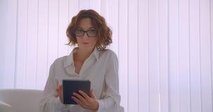 Zbliżenie portret dorosłej rudzielec caucasian bizneswoman patrzeje kamerę ono uśmiecha się szczęśliwie w szkłach używać pastylkę zdjęcie wideo