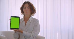 Zbliżenie portret dorosłej rudzielec caucasian bizneswoman używa pastylkę i pokazywać zieleń ekran kamery obsiadanie wewnątrz zbiory
