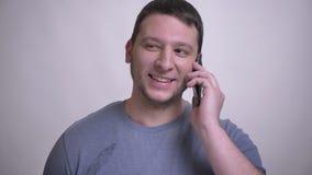 Zbliżenie portret dorosły atrakcyjny caucasian mężczyzna ma rozmowę telefoniczą ono uśmiecha się szczęśliwie z tłem odizolowywają zdjęcie wideo