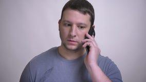 Zbliżenie portret dorosły atrakcyjny caucasian mężczyzna ma rozmowę telefoniczą z tłem odizolowywającym na bielu zbiory