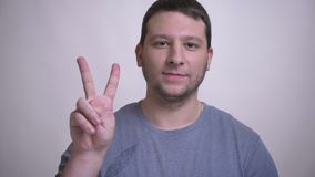 Zbliżenie portret dorosły atrakcyjny caucasian mężczyzna pokazuje dwa palca i ono uśmiecha się podpisuje patrzejący kamerę z zbiory wideo