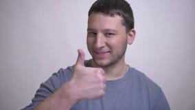 Zbliżenie portret dorosły atrakcyjny caucasian mężczyzna pokazuje kciuk w górę i ono uśmiecha się szczęśliwie patrzejący kamerę z zdjęcie wideo