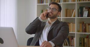 Zbliżenie portret dorosły pomyślny caucasian biznesmen w szkłach ma rozmowy telefoniczej obsiadanie przed laptopem zbiory wideo