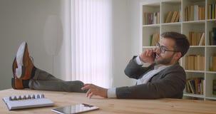 Zbliżenie portret dorosły przystojny brodaty caucasian biznesmen ma rozmowę telefoniczą z jego ciekami na stole w zbiory wideo