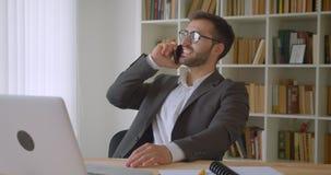 Zbliżenie portret dorosły przystojny brodaty caucasian biznesmen w szkłach ma rozmowy telefoniczej obsiadanie przed zbiory
