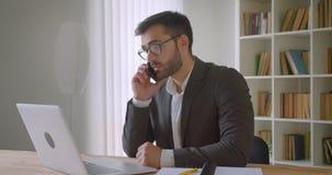Zbliżenie portret dorosły przystojny brodaty caucasian biznesmen w szkłach używać laptop wewnątrz i mieć rozmowę telefoniczą zdjęcie wideo