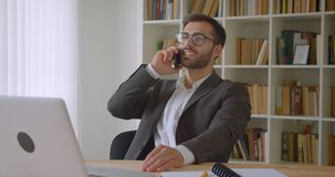 Zbliżenie portret dorosły przystojny caucasian biznesmen w szkłach ma rozmowy telefoniczej obsiadanie przed laptopem zbiory