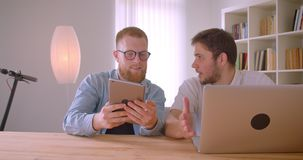 Zbliżenie portret dwa dorosłego caucasian biznesmena używa laptop ma dyskusję w indoors pastylkę i zbiory