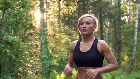 Zbliżenie portret dziewczyny atleta mięśniowa dziewczyna Jogging przy świtem w lato lasu zwolnionym tempie zbiory