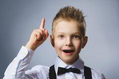 Zbliżenie portret gestykulujący dziecko na popielatym tle Chłopiec zakłada rozwiązanie lub pomysł zdjęcie stock