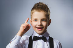 Zbliżenie portret gestykulujący dziecko na popielatym tle Chłopiec zakłada rozwiązanie lub pomysł fotografia royalty free