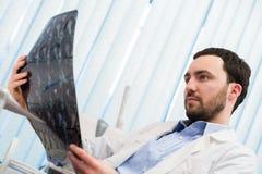 Zbliżenie portret intelektualny mężczyzna opieki zdrowotnej personel z białym labcoat, patrzeje móżdżkowego promieniowania rentge Zdjęcie Stock