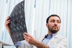 Zbliżenie portret intelektualny mężczyzna opieki zdrowotnej personel z białym labcoat, patrzeje móżdżkowego promieniowania rentge Obrazy Stock