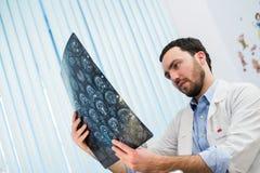 Zbliżenie portret intelektualny mężczyzna opieki zdrowotnej personel z białym labcoat, patrzeje móżdżkowego promieniowania rentge Fotografia Stock