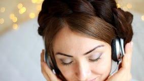 Zbliżenie portret kobieta słucha muzyczna piosenka z oczami w hełmofonach zamykał w światłach zbiory