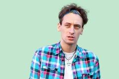 Zbliżenie portret mądry zaintrygowanie młody człowiek w przypadkowej błękitnej w kratkę pozycji i główkowanie koszula i kapitałki zdjęcia stock