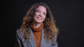 Zbliżenie portret młoda caucasian żeńska patrzeje kamera i ono uśmiecha się z odosobnionym pomyślna i ufna zbiory