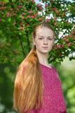 Zbliżenie portret młoda naturalna piękna rudzielec kobieta w fuksi bluzce pozuje przeciw kwitnąć drzewa z zamazanym zielonym fola Zdjęcia Stock