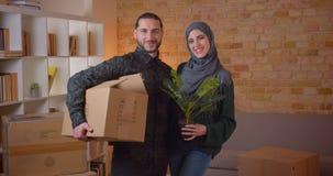 Zbliżenie portret młoda rozochocona muzułmańska para patrzeje kamery pozycję w niedawno kupującym mieszkaniu zbiory wideo