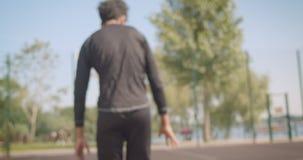 Zbliżenie portret młodego amerykanin afrykańskiego pochodzenia męski gracz koszykówki ustala patrzejący kamerę siedzi outdoors zdjęcie wideo