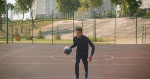 Zbliżenie portret młodego atrakcyjnego amerykanin afrykańskiego pochodzenia męski gracz koszykówki rzuca piłkę w obręcz outdoors  zbiory wideo