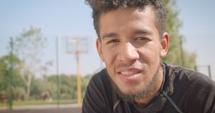 Zbliżenie portret młodego atrakcyjnego amerykanin afrykańskiego pochodzenia męski gracz koszykówki ustala patrzejący kamery obsia zbiory