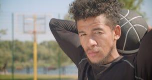 Zbliżenie portret młodego przystojnego amerykanin afrykańskiego pochodzenia męski gracz koszykówki patrzeje kamerę trzyma piłkę z zdjęcie wideo