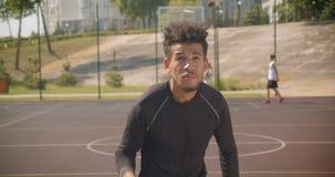 Zbliżenie portret młodego przystojnego amerykanin afrykańskiego pochodzenia męski gracz koszykówki rzuca piłkę w obręcz outdoors  zdjęcie wideo