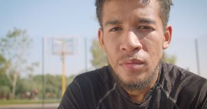 Zbliżenie portret młodego przystojnego amerykanin afrykańskiego pochodzenia męski gracz koszykówki ustala patrzejący kamery obsia zbiory wideo